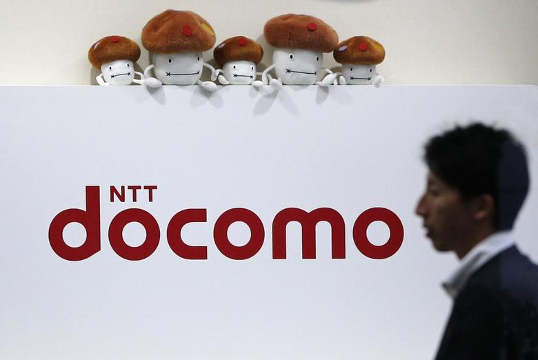A man walks past the logo of Japan's biggest mobile phone operator NTT Docomo at its shop in Tokyo July 3, 2013. REUTERS/Issei Kato