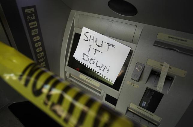 A sign on an ATM machine is seen at a Wells Fargo Bank on Broadway St. as demonstrators rally in a citywide general strike against Wall Street and police brutality in Oakland, California November 2, 2011. REUTERS/Stephen Lam