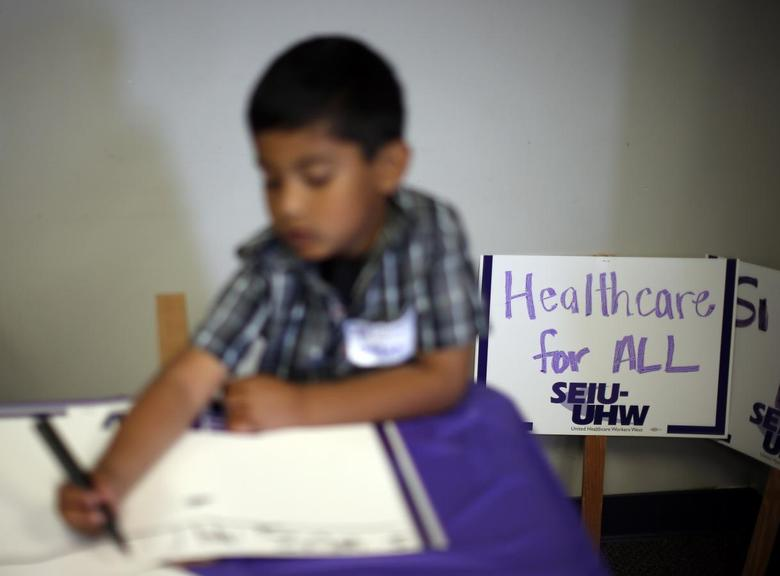 A boy draws signs at a health insurance enrolment event in Commerce, California March 31, 2014. REUTERS/Lucy Nicholson
