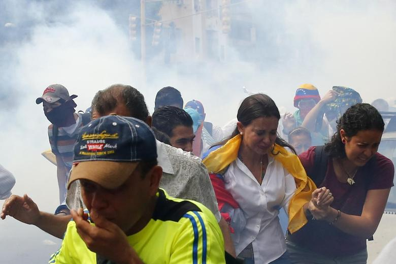Venezuelas opposition leader Maria Corina Machado runs away from tear gas after she tries to take her seat at the national assembly in Caracas April 1, 2014. REUTERS/Jorge Silva