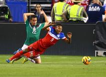 Apr 2, 2014; Glendale, AZ, USA; USA forward Julian Green (9) falls as he collides with Mexico defender Paul Aguilar (22) in the second half during a friendly match at University of Phoenix Stadium. The game ended in a 2-2 tie. Mandatory Credit: Mark J. Rebilas-USA TODAY Sports