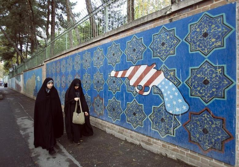 EDITORS' NOTE: Reuters and other foreign media are subject to Iranian restrictions on their ability to film or take pictures in Tehran. Iranian women walk past a mural outside the former U.S. embassy in Tehran November 4, 2009. REUTERS/Raheb Homavandi
