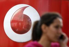 Женщина проходит мимо магазина Vodafone в Лондоне 2 сентября 2013 года. Британская Vodafone Group Plc откроет 150 магазинов и создаст 1.400 новых рабочих мест в Соединенном Королевстве в следующие 12 месяцев и потратит на эти цели 100 миллионов фунтов стерлингов ($166,33 миллиона). REUTERS/Stefan Wermuth