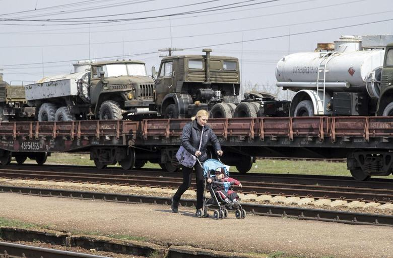 A woman walks with a pram along Ukrainian army vehicles on freight carriages ready to be sent from Crimea in the settlement of Gvardeiskoye near the Crimean city of Simferopol April 1, 2014. REUTERS/Stringer