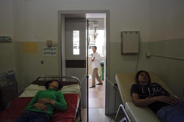 Garment workers recover at a hospital after fainting at a factory in Phnom Penh April 3, 2014. REUTERS/Samrang Pring