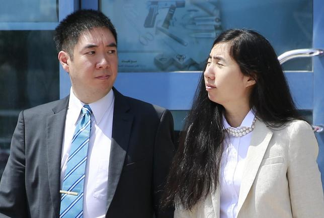 Matthew (L) and Grace Huang, a U.S. couple who were accused of murdering their adopted daughter Gloria, stand outside the entrance of the Court of First Instance after their trial in Doha, March 27, 2014. REUTERS/Mohammed Dabbous