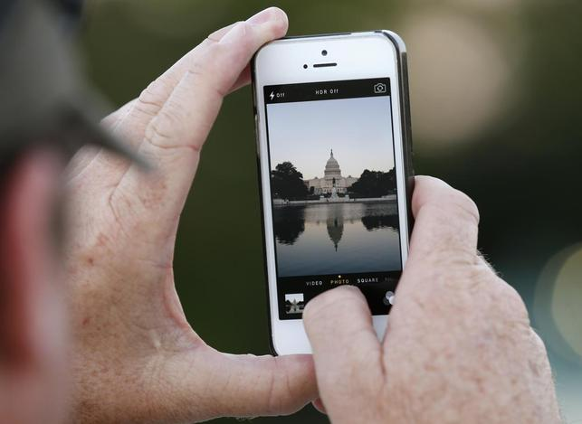 A man takes a photo of the U.S. Capitol, on the eve of a potential federal government shutdown, in Washington September 30, 2013. REUTERS/Kevin Lamarque