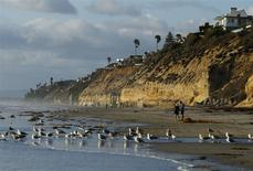 People walk along the beach in San Diego's North County beach town of Encinitas, California March 31, 2014. REUTERS/Mike Blake