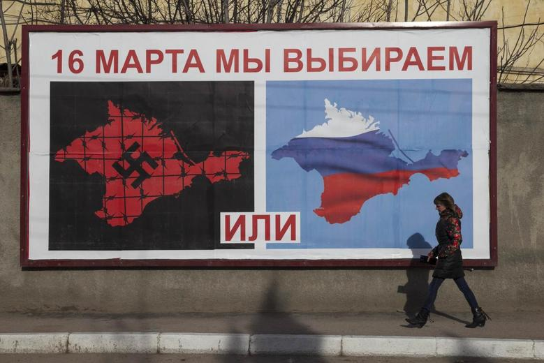A woman walking by a poster calling people to vote in the upcoming referendum, in the Crimean port city of Sevastopol March 10, 2014. REUTERS/Baz Ratner