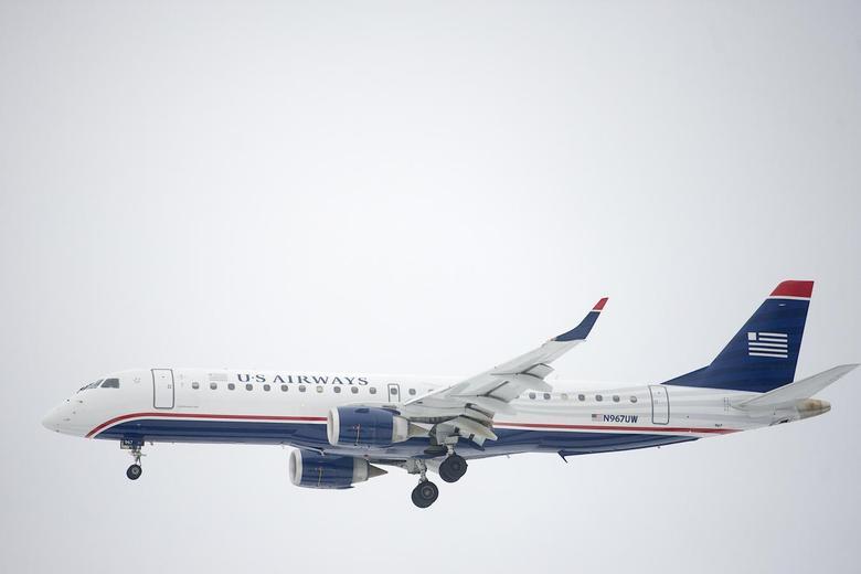 A US Airways Embraer ERJ-190 jet descends for landing at Philadelphia International Airport in Philadelphia, Pennsylvania on December 9, 2013. REUTERS/Mark Makela