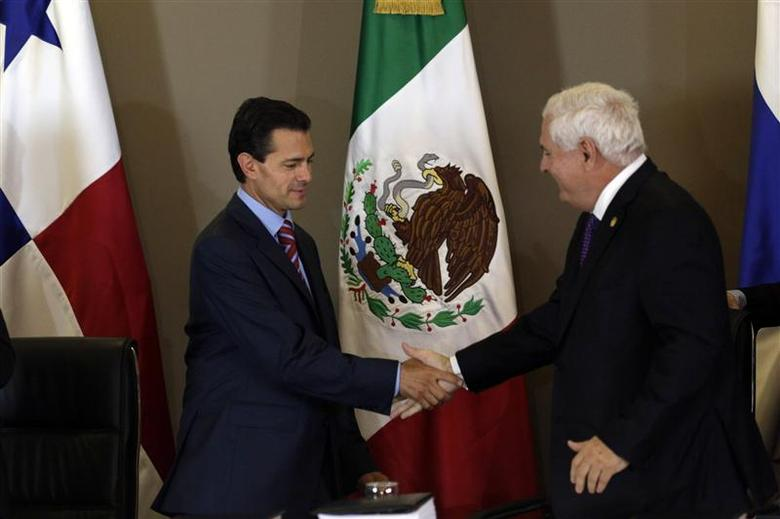 Mexico's President Enrique Pena Nieto (L) and his Panamanian counterpart Ricardo Martinelli shake hands after signing a free trade agreement between the two countries during the last day of the World Economic Forum on Latin America in Panama City April 3, 2014. REUTERS/ Carlos Jasso