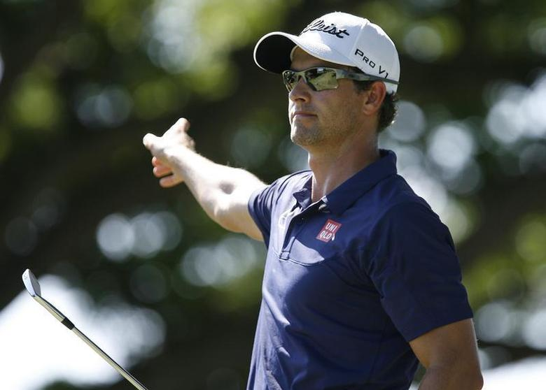 Adam Scott of Australia points as he follows his ball after teeing off on the second hole during the final round of the Sony Open golf tournament at Waialae Country Club in Honolulu, Hawaii, January 12, 2014. REUTERS/Hugh Gentry