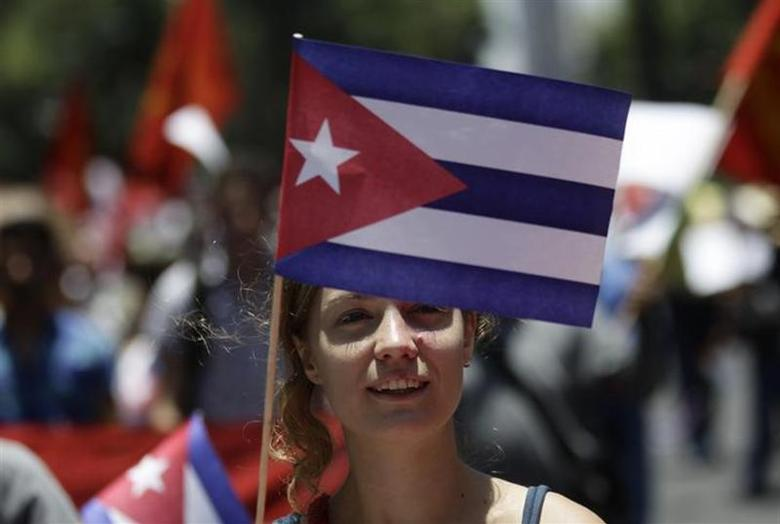 A woman holds up a Cuban flag as they walk with other people from civil organizations and workers from different unions in Cuba, near the U.S. embassy in Mexico City July 27, 2013. REUTERS/Henry Romero/Files