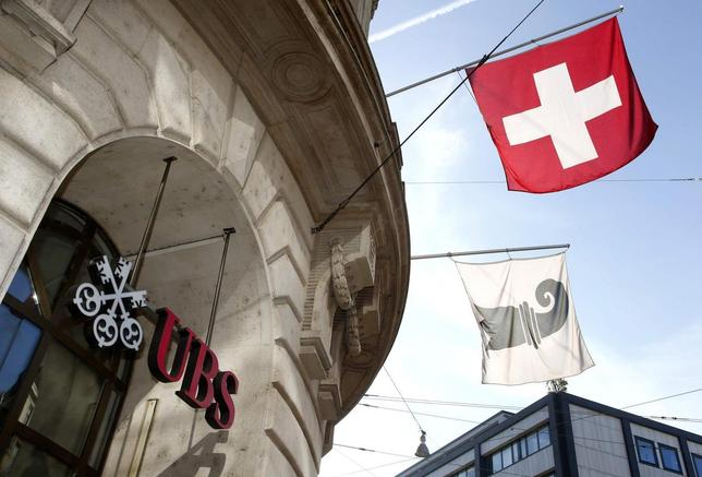 A Swiss national flag (top) and a flag of the city of Basel fly over the entrance of a branch office of Swiss bank UBS in Basel October 22, 2013. REUTERS/Arnd Wiegmann