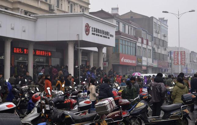 People gather in front of a branch of Jiangsu Sheyang Rural Commercial Bank, in Yancheng, Jiangsu province, March 25, 2014. REUTERS/Stringer