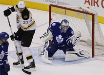 Apr 3, 2014; Toronto, Ontario, CAN; Toronto Maple Leafs goaltender James Reimer (34) makes a save on a shot tipped by Boston Bruins defenseman Zdeno Chara (33) at the Air Canada Centre. Toronto defeated Boston 4-3 in overtime. Mandatory Credit: John E. Sokolowski-USA TODAY Sports