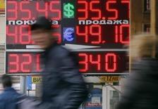 Люди проходят мимо пункта обмена валют в Москве 3 апреля 2014 года. Рубль утром пятницы стабилен к доллару и бивалютной корзине в ожидании трудовой статистики США, немного подорожал к евро, отражая динамику форекса; вечером участники рынка не исключают расширения волатильности после американской публикации и перед выходными днями. REUTERS/Maxim Shemetov