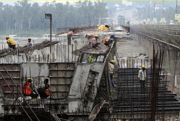 Labourers work at the construction site of a highway bridge on the outskirts of Jammu August 31, 2013. REUTERS/Mukesh Gupta/Files