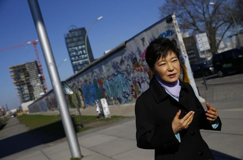 South Korean President Park Geun-hye looks at the exhibition 'DMZ-Gruenes Band' during a visit to the East Side Gallery in Berlin March 27, 2014. REUTERS/Kai Pfaffenbach