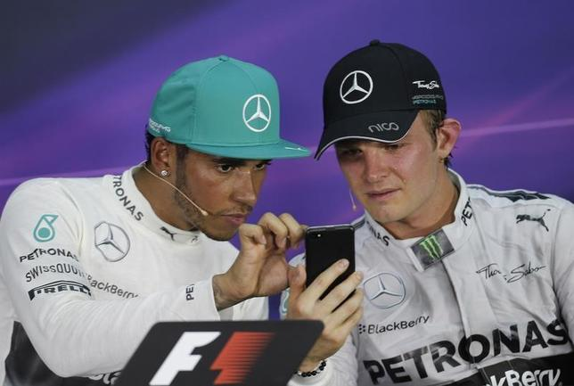 Race winner Mercedes Formula One driver Lewis Hamilton of Britain looks at the mobile device of team mate second-placed Nico Rosberg of Germany after the Malaysian F1 Grand Prix at Sepang International Circuit outside Kuala Lumpur, March 30, 2014. REUTERS/Samsul Said