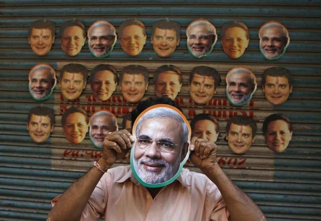 A vendor wears a mask of Narendra Modi, prime ministerial candidate for Bharatiya Janata Party (BJP) and Gujarat's chief minister, to attract customers at his stall selling masks of political leaders ahead of general election in Chennai April 3, 2014. REUTERS/Babu
