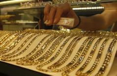 Золотые цепочки на витрине магазина в Ханое 5 июня 2013 года. Цены на золото растут накануне отчета о занятости в США, но снизятся за неделю из-за подъема на фондовых рынках и оптимизма по поводу американской экономики. REUTERS/Kham