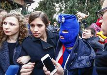 Russian punk band Pussy Riot members Maria Alyokhina (L) and Nadezhda Tolokonnikova (2nd L) along with a masked member speak to journalists during the 2014 Sochi Winter Olympics, in Adler February 20, 2014. REUTERS/Shamil Zhumatov