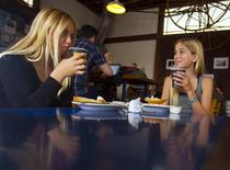 Twelve-year-old certified yoga instructor Jaysea DeVoe (R) enjoys a hot chocolate with her friend Miely at a coffee shop in Encinitas, California March 24, 2014. REUTERS/Mike Blake