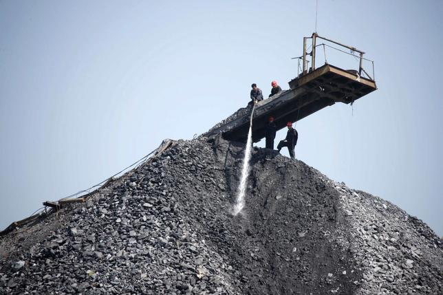 Employees work on a pile of coal gangue in Huaibei, Anhui province, September 17, 2013. REUTERS/Stringer