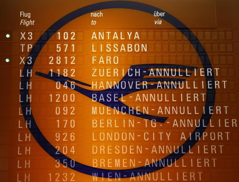 A picture taken with the multiple exposure function of the camera shows cancelled flights on a flight schedule board and the logo of German air carrier Lufthansa at the Fraport airport in Frankfurt in this picture illustration taken on April 2, 2014. REUTERS/Kai Pfaffenbach