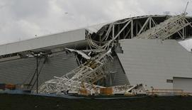 "Workers stand near a crane that collapsed on the site of the Arena Sao Paulo stadium, known as ""Itaquerao"", which will host the opening soccer match of the 2014 World Cup, in Sao Paulo November 27, 2013. REUTERS/Nacho Doce"