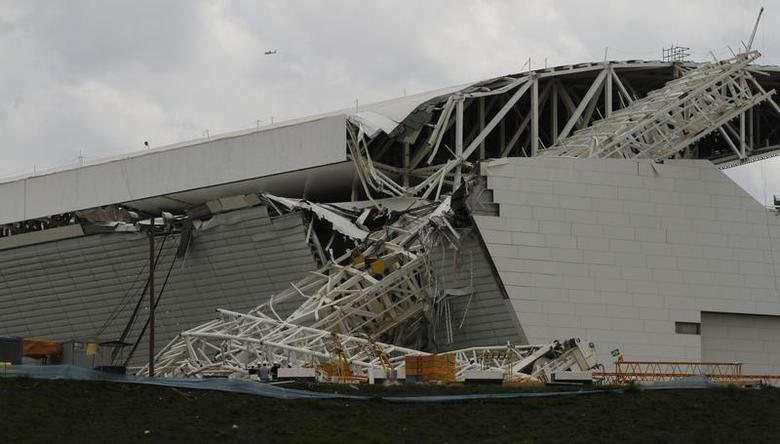 Workers stand near a crane that collapsed on the site of the Arena Sao Paulo stadium, known as ''Itaquerao'', which will host the opening soccer match of the 2014 World Cup, in Sao Paulo November 27, 2013. REUTERS/Nacho Doce