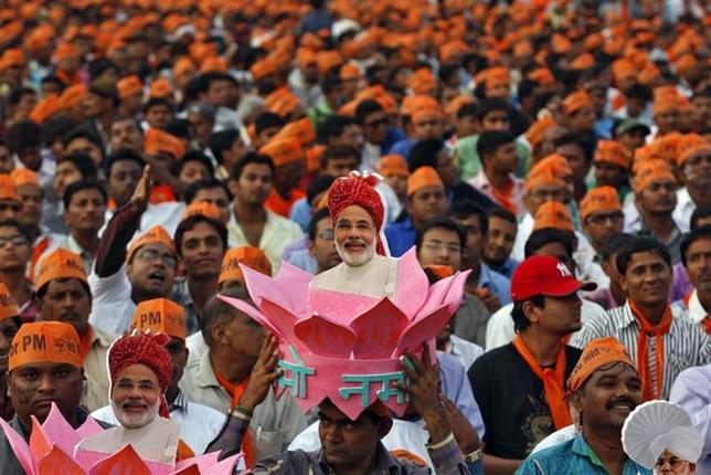 A supporter of Gujarat's chief minister and Hindu nationalist Narendra Modi, the prime ministerial candidate for Bharatiya Janata Party (BJP), wears a headgear with a portrait of Modi during a rally being addressed by Modi ahead of the 2014 general elections, in Ahmedabad February 20, 2014. REUTERS/Amit Dave/Files