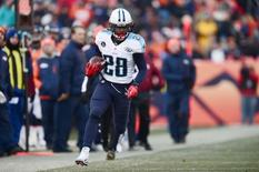 Dec 8, 2013; Denver, CO, USA; Tennessee Titans running back Chris Johnson (28) rushes on fourth down in the second quarter against the Denver Broncos at Sports Authority Field at Mile High. Ron Chenoy-USA TODAY Sports - RTX16AE1