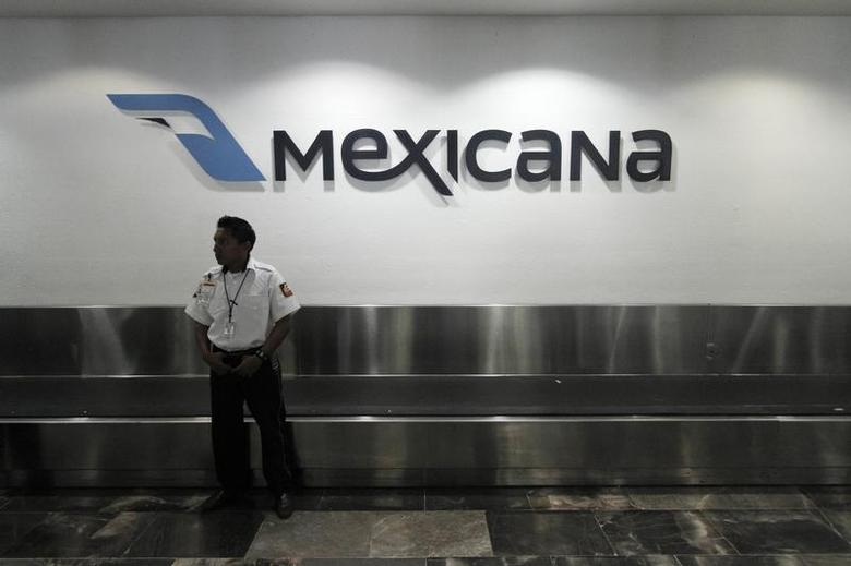 A security guard stands behind a counter of Mexicana de Aviacion at Cancun's international airport August 28, 2010. REUTERS/Gerardo Garcia