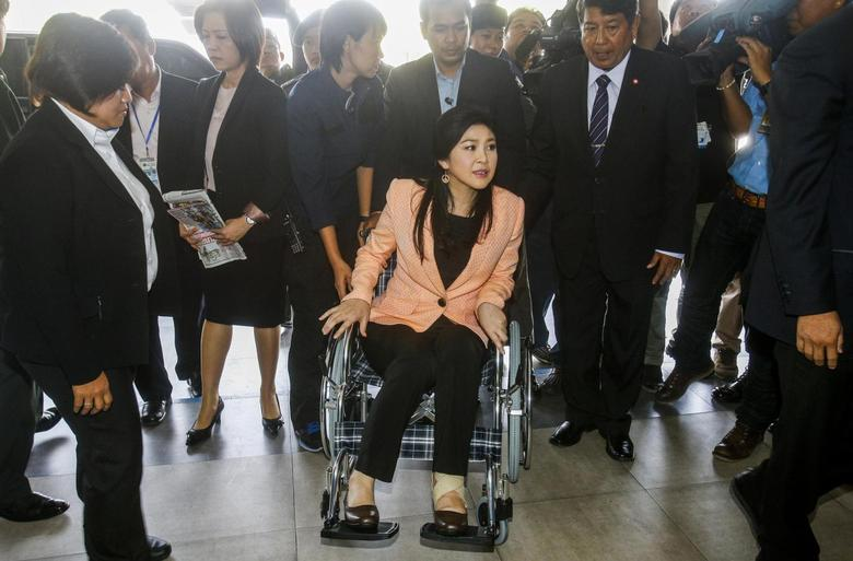 Thailand's Prime Minister Yingluck Shinawatra (C) arrives on a wheelchair at the Royal Police Cadet Academy in Nakorn Pathom province, March 18, 2014. REUTERS/Athit Perawongmetha
