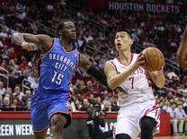 Apr 4, 2014; Houston, TX, USA; Houston Rockets guard Jeremy Lin (7) drives to the basket during the first quarter as Oklahoma City Thunder guard Reggie Jackson (15) defends at Toyota Center. Mandatory Credit: Troy Taormina-USA TODAY Sports