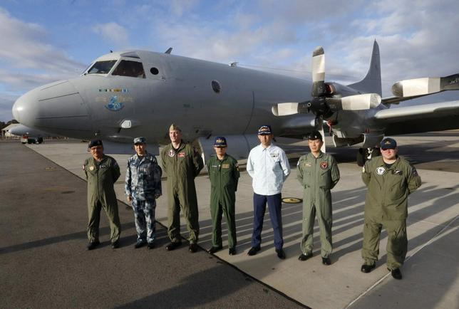 Leaders of the international forces currently based in Perth to search for Malaysia Airlines flight MH370 stand in front of a Royal Australian Air Force AP-3C Orion aircraft before a visit by Australia's Prime Minister Tony Abbott at RAAF Base Pearce near Perth March 31, 2014. REUTERS/Jason Reed