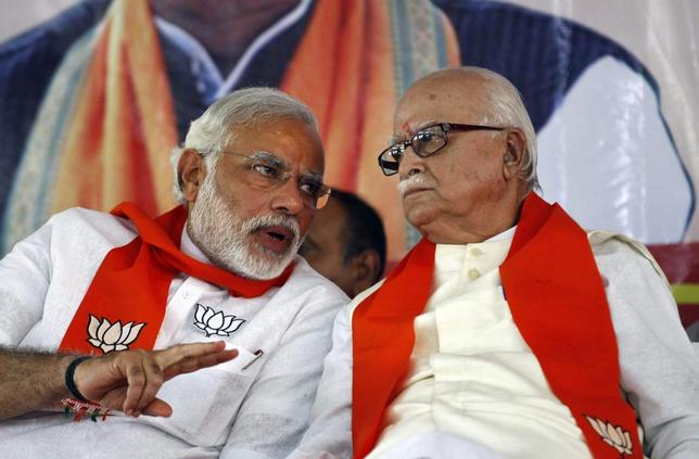 A leader of India's main opposition Bharatiya Janata Party (BJP), Lal Krishna Advani (R), listens to BJP prime ministerial candidate Narendra Modi during a workers' party meeting ahead of the general election, at Gandhinagar in the western Indian state of Gujarat April 5, 2014. REUTERS/Amit Dave