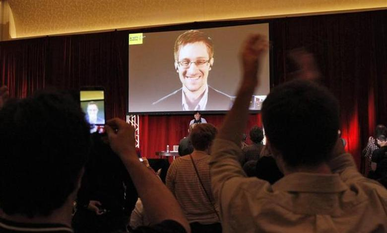 Supporters of Amnesty International cheer and shoot mobile phone videos as accused government whistleblower Edward Snowden is introduced via teleconference during the Amnesty International Human Rights Conference 2014 in Chicago, April 5, 2014. REUTERS/Frank Polich