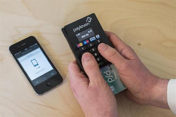 Konstantin Wolff, co-founder of the Payleven mobile payment service provider, demonstrates the Chip and Pin mobile card payment service using a smartphone and a bluetooth chip card reader at the company's office in Berlin March 6, 2013. REUTERS/Thomas Peter/Files