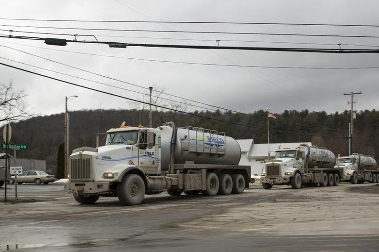 A line of trucks carrying water to Natural gas rigs make their way across the sprawling network of two lane roads between small towns to make almost constant deliveries to continue the hydraulic fracturing process used to gather natural gas in Monroeton, Pennsylvania, January 13, 2013. REUTERS/Brett Carlsen