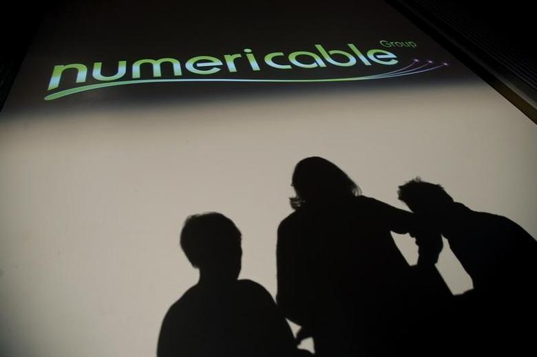 Shadows are pictured in front of the logo of French cable operator Numericable during the company's 2013 annual results presentation in Paris March 12, 2014. REUTERS/Jacky Naegelen