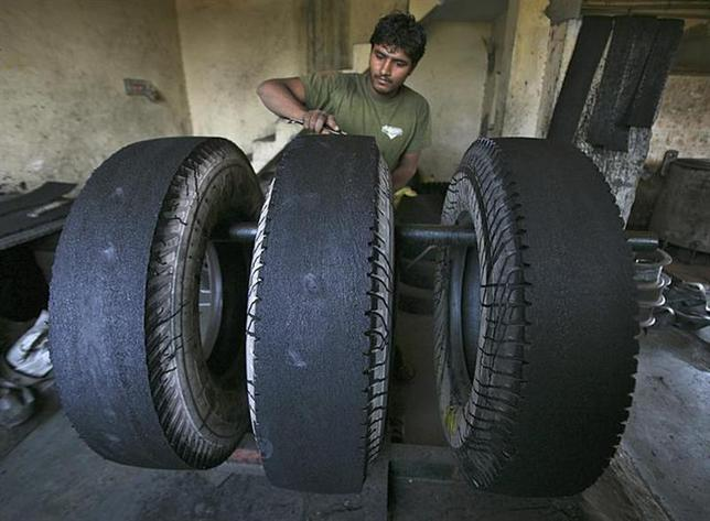 A worker retreads a used rubber tyre at a workshop on the outskirts of Jammu October 29, 2013. REUTERS/Mukesh Gupta/Files