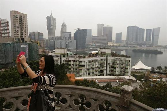 A woman takes a photo on Penha Hill, overlooking the Macau peninsula March 17, 2014. REUTERS/Bobby Yip/Files