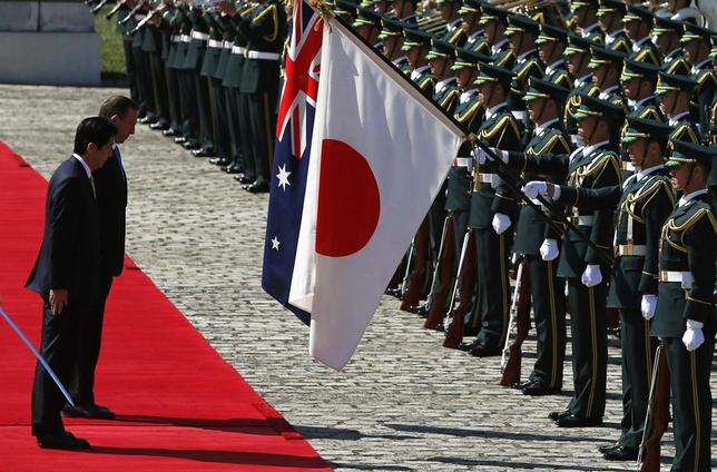 Australia's Prime Minister Tony Abbott (2nd L) bows to Australian and Japanese national flags as he reviews a guard of honour with Japan's Prime Minister Shinzo Abe (L) during a welcome ceremony hosted by Abe at the state guest house in Tokyo April 7, 2014. REUTERS/Yuya Shino