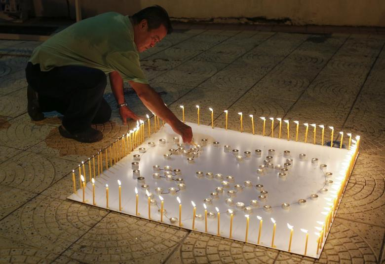 A man places a candle on a white board spelling out ''MH370'' during a candlelight vigil for the the missing Malaysia Airlines flight, in Kuala Lumpur April 6, 2014. REUTERS/Samsul Said