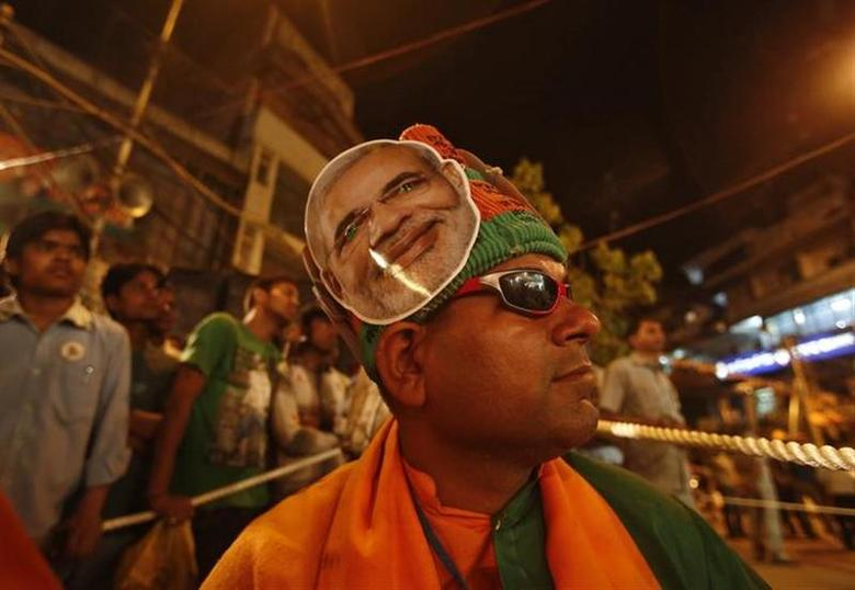 A supporter of India's main opposition Bharatiya Janata Party (BJP) wears a headgear carrying a portrait of Hindu nationalist Narendra Modi, prime ministerial candidate for BJP during a public meeting being addressed by BJP leader Lal Krishna Advani, ahead of the general elections in the old quarters of Delhi April 4, 2014. REUTERS/Anindito Mukherjee
