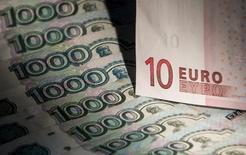 Купюры валют евро и рубль в Москве 17 февраля 2014 года. Рубль утром понедельника подешевел до первого подкоридора интервенционных продаж валюты Центробанком на фоне негативной динамики мировых рынков и нефтяных котировок. REUTERS/Maxim Shemetov