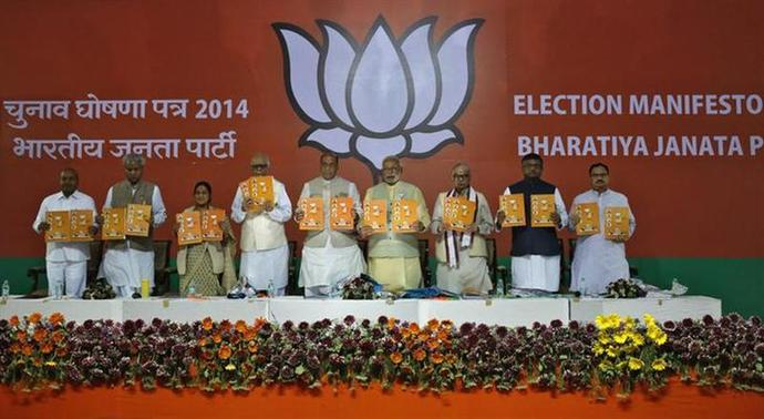 Hindu nationalist Narendra Modi (4th R), the prime ministerial candidate for Bharatiya Janata Party (BJP), along with other party leaders hold copies of election manifesto in New Delhi April 7, 2014. REUTERS/Anindito Mukherjee